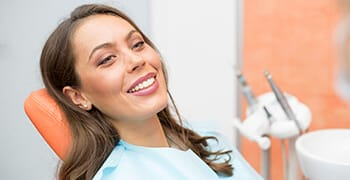 Woman in dental chair with lovely smile