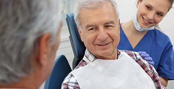 Older man with dentist and assistant