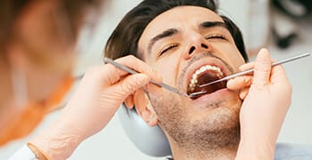 Man in dental chair examined by dentist