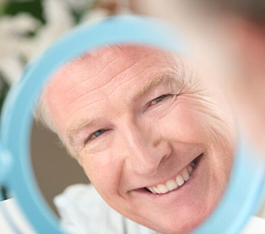 Older man smiling in mirror