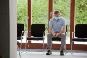 older man wearing face mask and sitting in waiting room