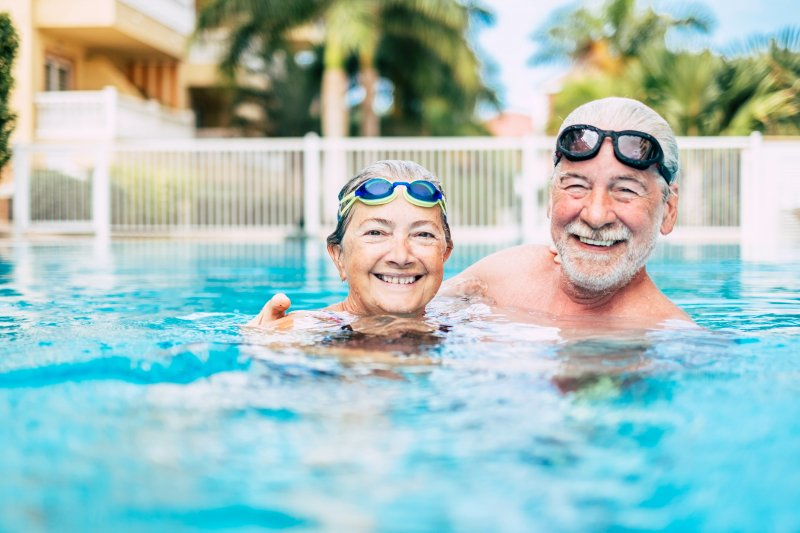 Elderly couple smiling in swimming pool