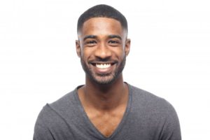 young man in black shirt smiling with perfect teeth thanks to cosmetic dentist in Tallahassee